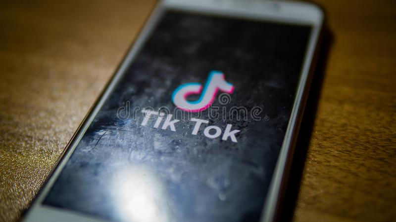 Close up view of the Tik Tok logo on an android smartphone with wooden table background stock image