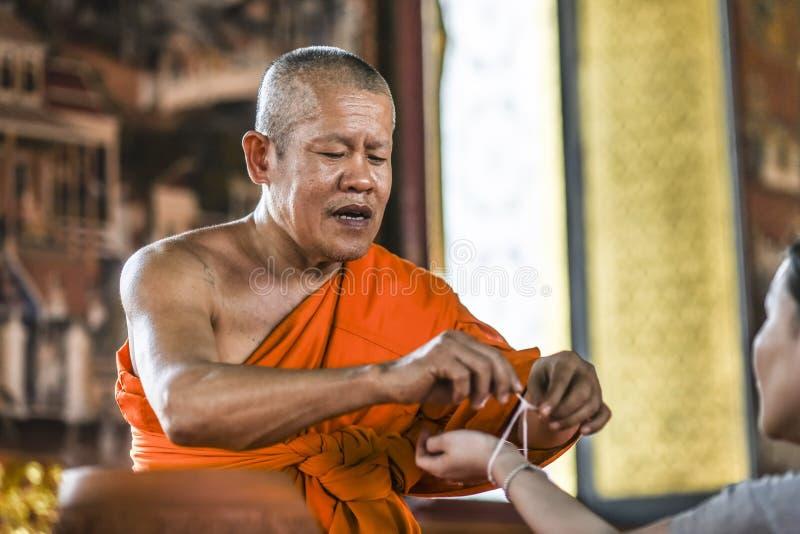 Bangkog,泰国, 2016年3月4日:tieding在一只手上的一条圣洁螺纹的修士在寺庙 免版税库存图片