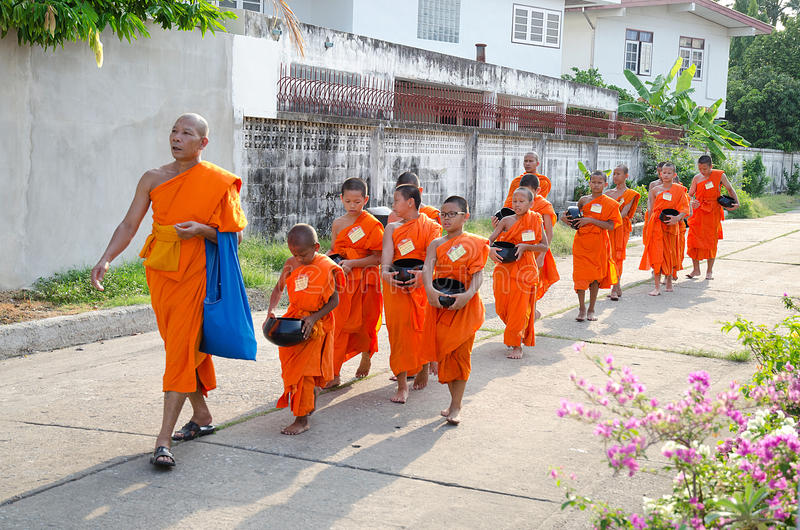 BANGKOK - APR 2014: Buddhist Monk and novice walking for receive food on April 20, 2014 in Bangkok,Thailand. royalty free stock photo