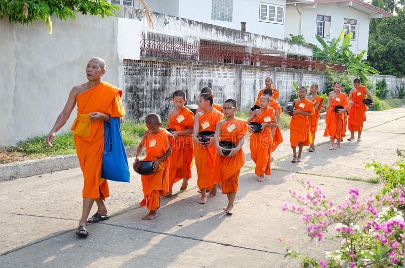 BANGKOK - APRIL 2014: Buddhistischer Mönch und der Anfänger, die für geht, empfangen Lebensmittel am 20. April 2014 in Bangkok, T lizenzfreies stockfoto