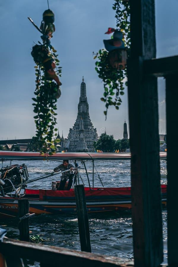Bangkok 12 14 18: Barkasskaptenen kontrollerar hans barkass i floden Wat Arun Temple i bakgrunden royaltyfri foto