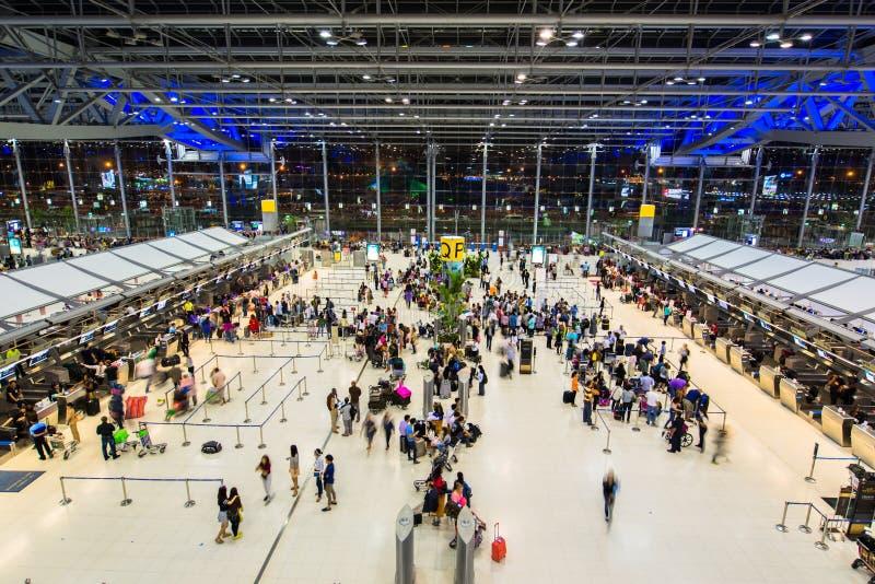BANGKOK - 4 de abril pasajeros que comprueban el horario de vuelo en cartas del aeropuerto en el aeropuerto de Suvarnabhumi, el 4 fotos de archivo libres de regalías