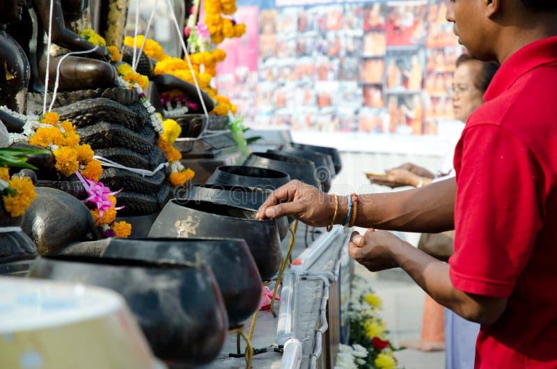 BANGKOK - DEC 2013: boeddhistische dalingsmuntstukken in de aalmoeskom van de monnik royalty-vrije stock afbeelding