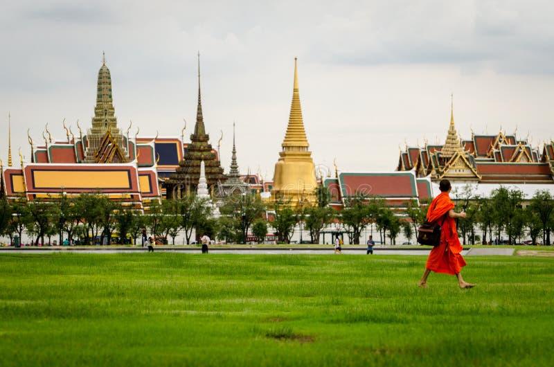 Bangkok den Bhuddist munken som går i Sanam Luang, parkerar med Wat Phra Kaeo arkivfoto