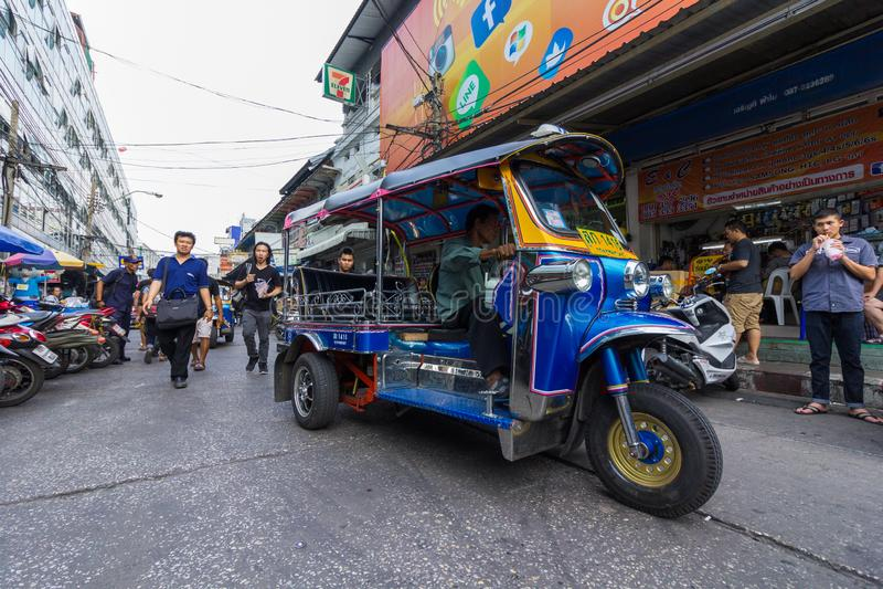 BANGKOK - JANUARI 16, 2017: Een three-wheeled tuk tuk taxi?t aandrijving langs een weg in Klongthom-Markt Bangkok, Thailand stock afbeeldingen