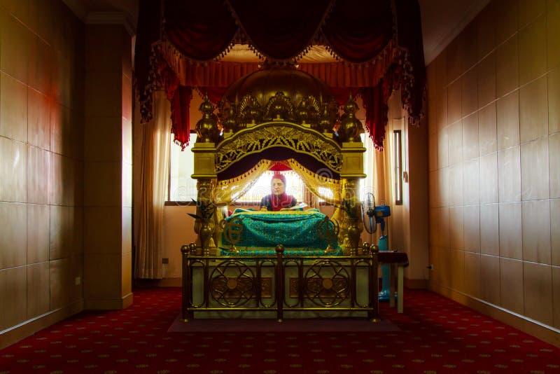 En kvinnaSikh vallfärdar suttet be i rum på den Gurdwara Siri guruen Singh Sabha. fotografering för bildbyråer