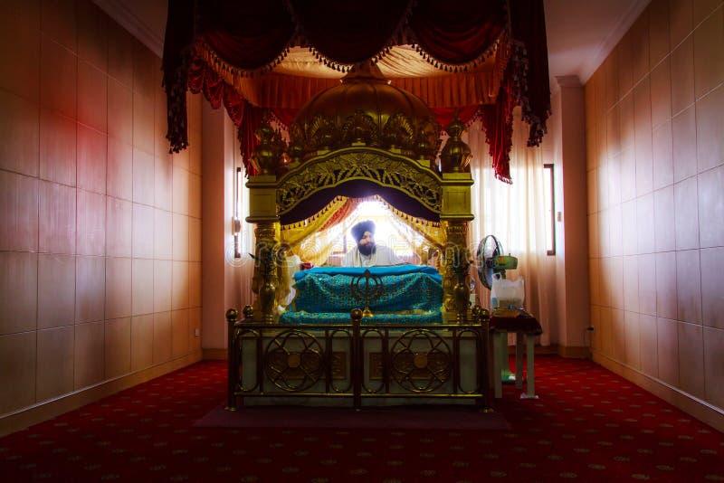 Sikhen vallfärdar suttet be i rum på den Gurdwara Siri guruen Singh Sabha. royaltyfri fotografi