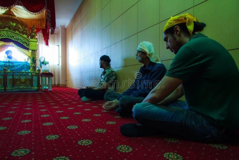 Sikhen vallfärdar suttet i rum lyssnar be på den Gurdwara Siri guruen Singh Sabha. royaltyfria foton