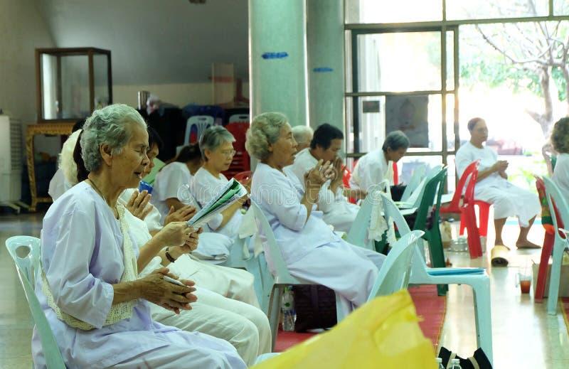Bangkok, Tailandia - 1° marzo 2018 gli anziani asiatici in vestito bianco stanno pregando un giorno importante fotografia stock libera da diritti