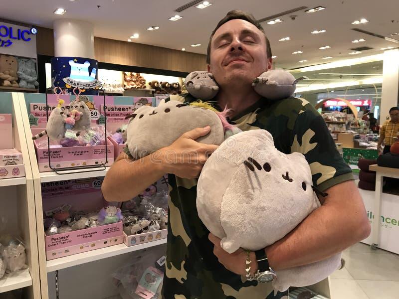 BANGKOK, TAILANDIA - 16 APRILE 2018: L'uomo gode dei giocattoli del gatto della peluche di Pusheen in Asia immagini stock libere da diritti
