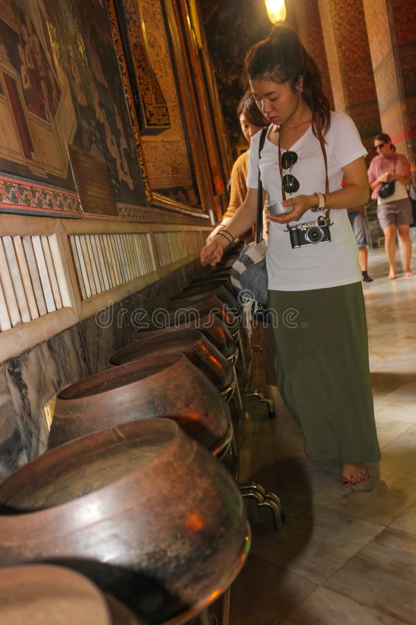 Bangkok, Tailandia - 29 aprile 2014 Monete tailandesi dei depositi della donna come offerta in una ciotola di monaco al tempio de immagini stock libere da diritti