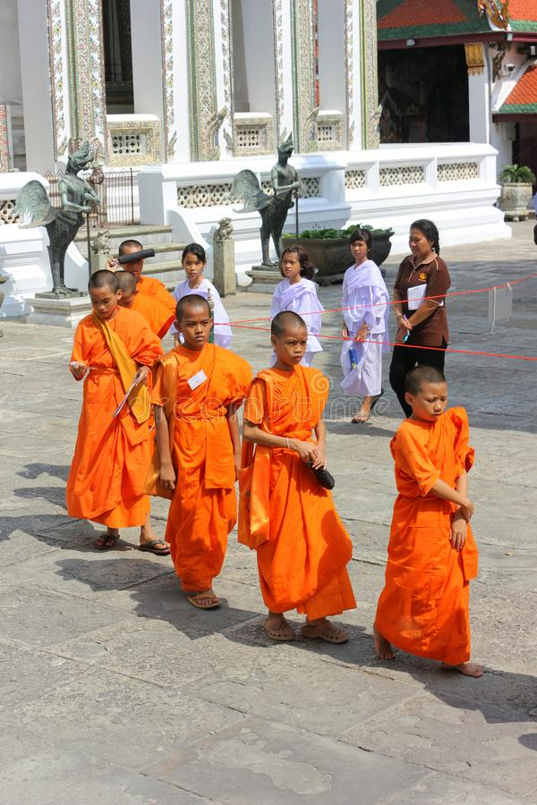 Bangkok, Tailandia - 29 de abril de 2014 Grupo de monjes asiáticos que caminan a través del templo de Emerald Buddha en Tailandia imágenes de archivo libres de regalías