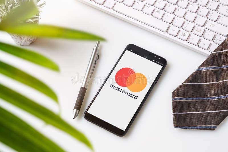 Bangkok, Tailandia - 6 de agosto de 2019: Vista superior del escritorio de oficina con el logotipo de Mastercard en Smartphone Ma fotografía de archivo libre de regalías