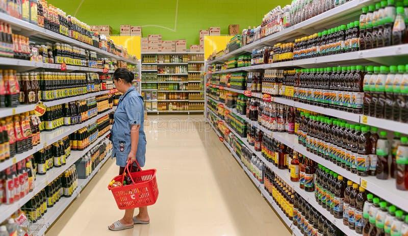 BANGKOK, TAILANDIA - 16 DE DICIEMBRE: Tiendas mayores no identificadas de la mujer para la salsa en la sección de la salsa de soj foto de archivo libre de regalías