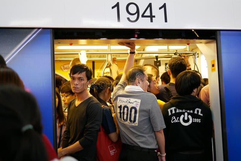 BANGKOK, TAILANDIA - 13 DE ENERO DE 2018: Pasajeros apretados llenos que embalaron en el skytrain del BTS en la plataforma sobre  foto de archivo libre de regalías