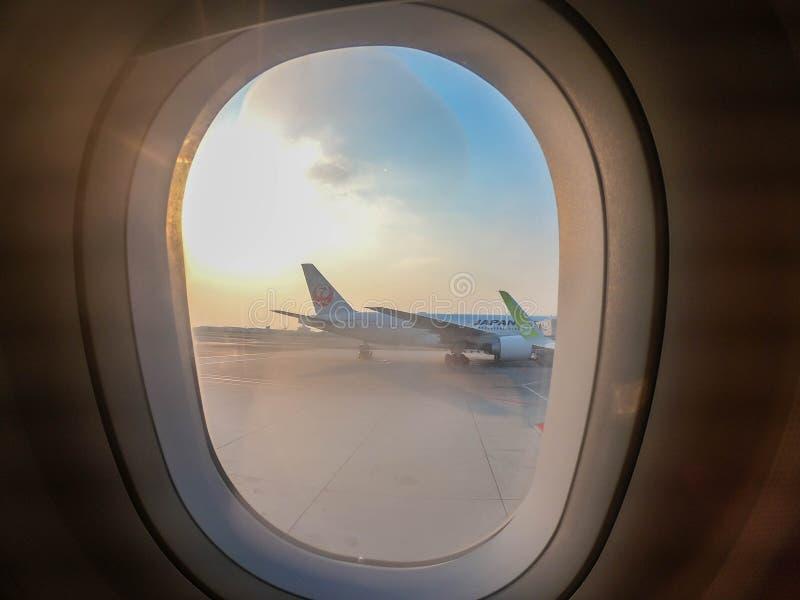 Bangkok/Tailandia - 12 de febrero de 2019: sombra de ventana del pasajero en aeroplano con Japan Airlines y los aviones S7 imagen de archivo libre de regalías