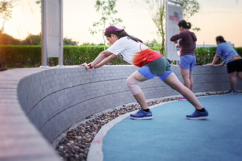 BANGKOK, TAILANDIA - 29 DE JUNIO: La mujer innomada realiza estiramientos del calentamiento antes de ejercicio en el parque Bangk fotos de archivo libres de regalías