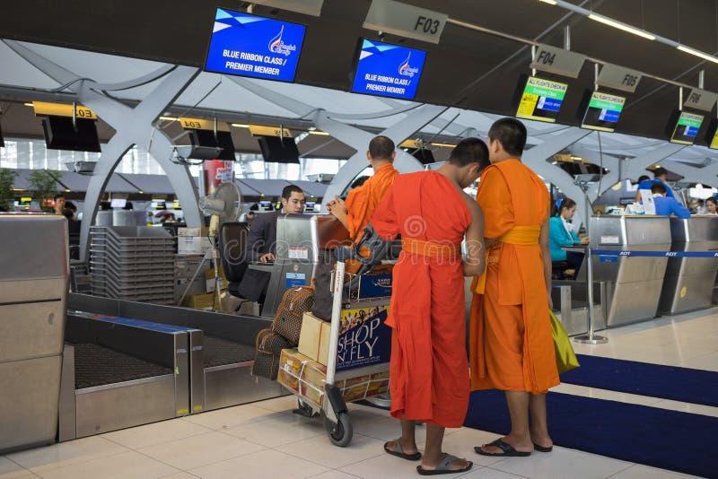 Bangkok, Tailandia - 28 de junio de 2015: Monjes jovenes en el mostrador de facturación, línea primera del miembro, en el aeropue foto de archivo