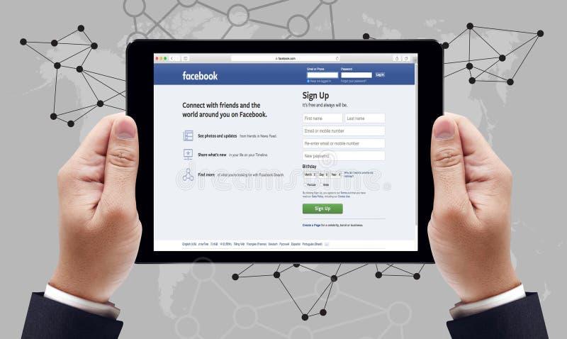 Bangkok, Tailandia - 10 de marzo de 2015: Hombre en un ipad que hojea Facebook fotografía de archivo