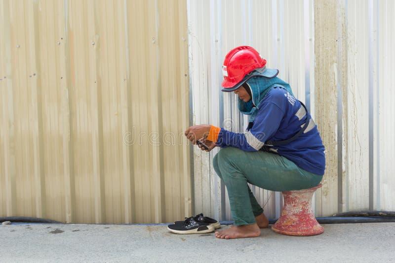 BANGKOK/TAILANDIA - 26 DE MARZO DE 2019:Un trabajador tiene relajar tiempo con el teléfono fotografía de archivo libre de regalías
