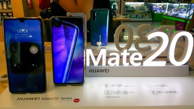 BANGKOK, TAILANDIA - 11 DE MAYO DE 2019: Manos en el odio de Huawei 20 series que muestran la recepción y la pantalla de las cara foto de archivo