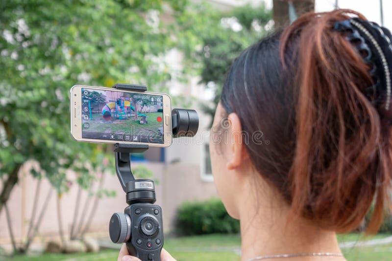 BANGKOK TAILANDIA - 26 DE MAYO: Vídeo innomado de los expedientes de la mujer usando un smartphone del Samsung Galaxy en un cardá fotografía de archivo libre de regalías