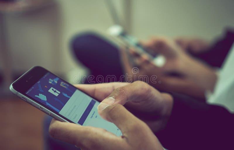 Bangkok, Tailandia - 11 de octubre de 2017: la mano está presionando la pantalla de Facebook en la manzana iphone6 fotos de archivo