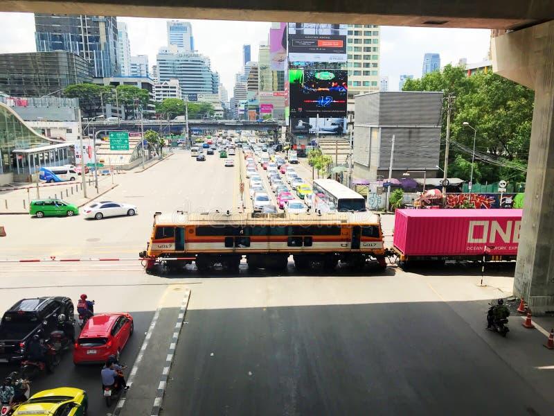 Bangkok, Tailandia - 7 de octubre de 2018: Muchos coches que esperan el tren para pasar la intersección del camino de Asoke-dinda fotos de archivo libres de regalías