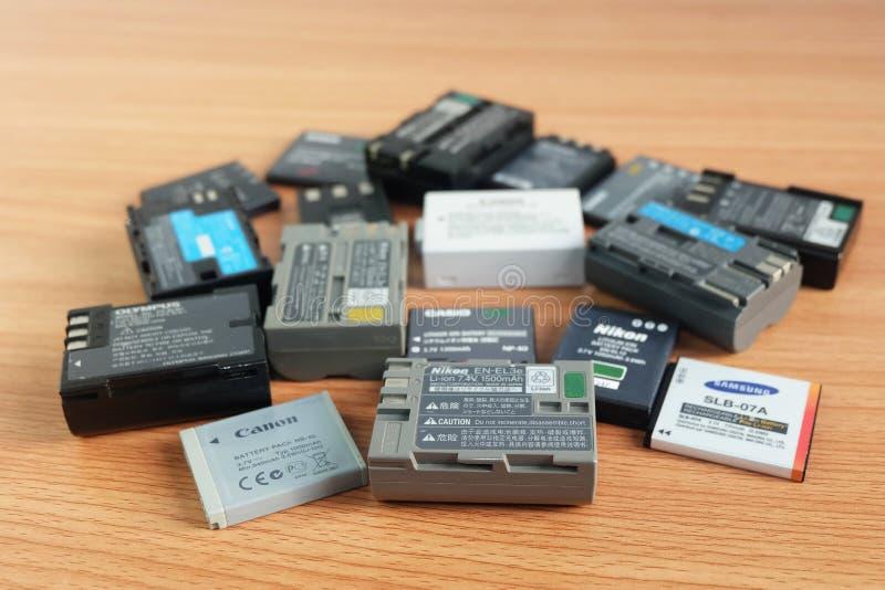 BANGKOK, TAILANDIA - 14 de septiembre de 2018: Batería usada para la cámara compacta y dslr en muchas marcas en de madera imagen de archivo libre de regalías