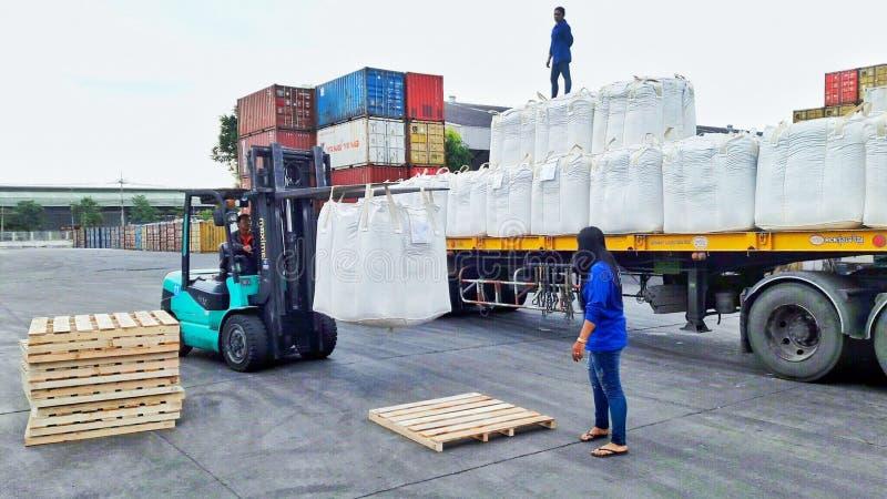 Bangkok, Tailandia 16 de septiembre de 2017: Los trabajadores descargan bolsos enormes del remolque a la pelotilla de madera en l imagen de archivo