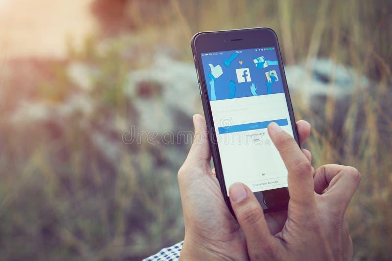 Bangkok, Tailandia - 26 febbraio 2018: le donne passano sta premendo lo schermo di Facebook sulla mela iphone6 sul prato fotografia stock