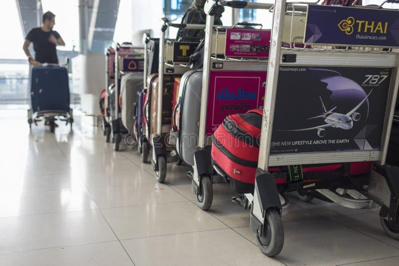 Bangkok, Tailandia - 28 giugno 2015: I carrelli impilati hanno caricato con i bagagli contro il passeggero maschio che spinge il  immagini stock