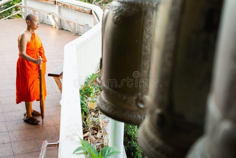 Bangkok, Tailandia - marzo de 2019: situación del monje budista al lado de las campanas en el templo de oro de Buda fotografía de archivo