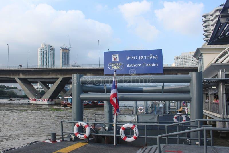 Bangkok, Tailandia - octubre de 2017: Embarcadero vacío de Sathorn en la conexión con BTS Saphan Taksin Bandera tailandesa en pol fotografía de archivo
