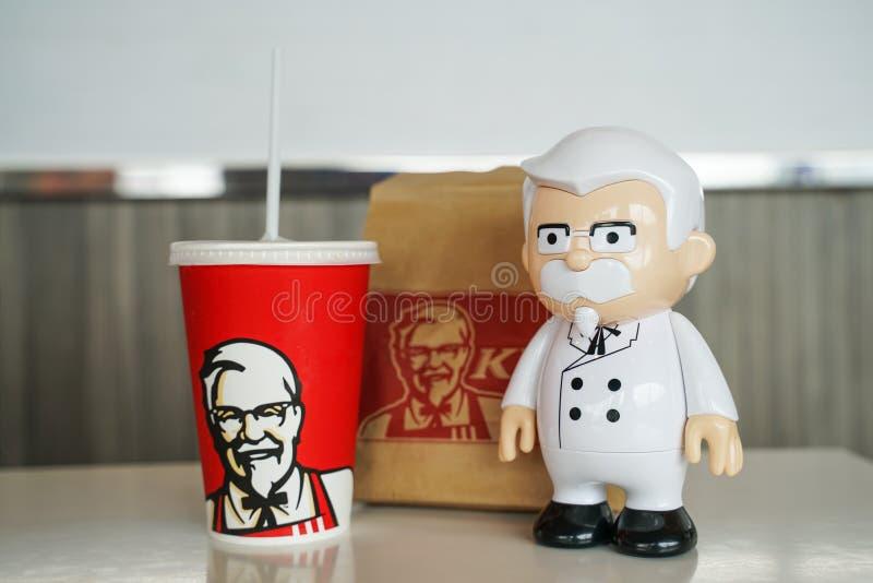 BANGKOK, TAILANDIA septiembre 15,2018: Muñeca de la estatua de coronel Harland Sanders con la bebida fría borrosa de KFC fotos de archivo libres de regalías