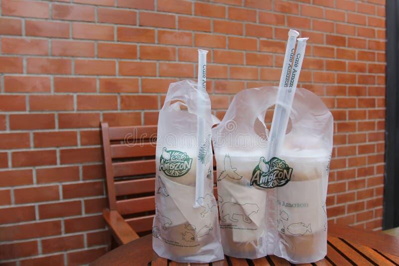 Bangkok, Tajlandia: Jane 13, 2018, Lodowa kawa w torbie cukierniany «Amazon na drewnianym stole w cukiernianym Amazon fotografia royalty free