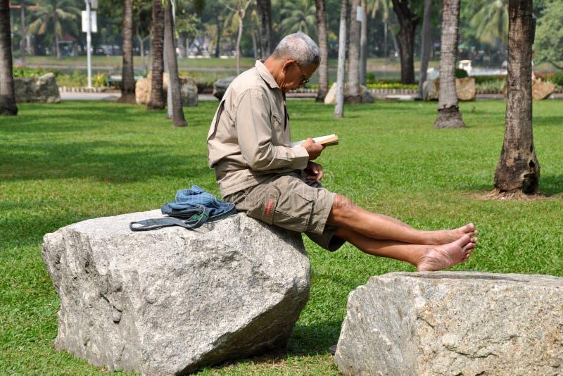 Bangkok, Tajlandia: Mężczyzna czytanie w Lumphini parku zdjęcia stock
