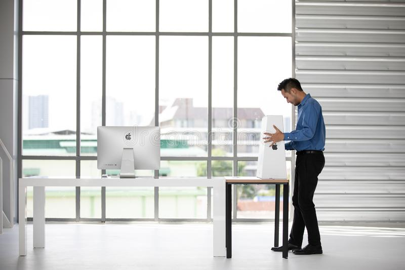 BANGKOK TAJLANDIA, MAJ, - 05, 2018: Azjatycki młody biznesmen unbox dwa nowego iMac komputeru w biurze i tworzył Komputer Apple w obraz royalty free