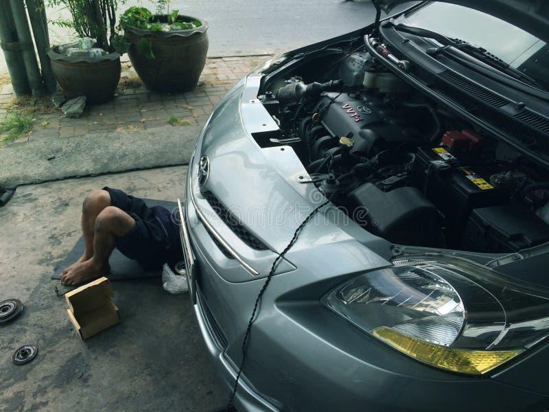 Bangkok Tajlandia, Marzec, - 6, 2017: Azjatycki auto mechanik pracuje pod samochodem przy garażem naprawiać obraz stock