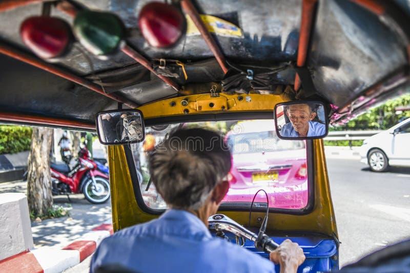 Bangkok, Tajlandia, Marzec 3, 2016: Tuku tuku kierowcy stary jeżdżenie przez Bangkok z twarzy wewnątrz inside samochodowym lustre zdjęcie stock