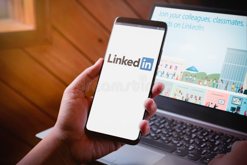 Bangkok Tajlandia, Sierpień, - 5, 2019: Ręki trzyma Smartphone z LinkedIn logo na ekranie i LinkedIn stroną internetową na laptop obrazy royalty free