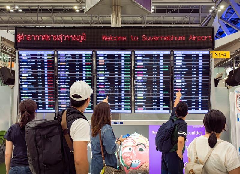 BANGKOK, THAÏLANDE - 26 AOÛT : Les voyageurs regarde l'horaire de programme de vol l'aéroport international de Suvarnabhumi à Ban photographie stock libre de droits