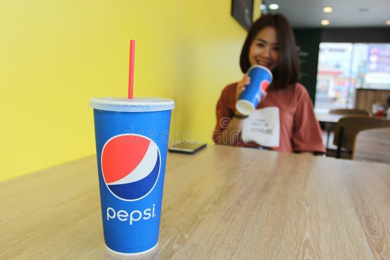 Bangkok, Thaïlande : Juillet 07,2018 : Boisson produite par PepsiCo sur la boisson en bois pepsi-cola de table et de jeune femme  photos libres de droits