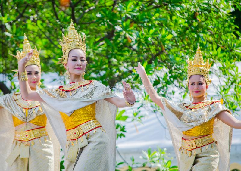 Thai traditional dance with beautiful woman on golden cultural costume performing on the stage for Songkran festival. stock photo