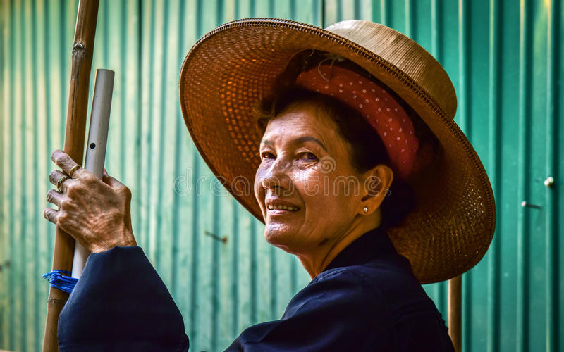 Bangkok / Thailand – January 20, 2017: Expression of an old Asian woman working in a boat in the floating market near Bangkok royalty free stock image