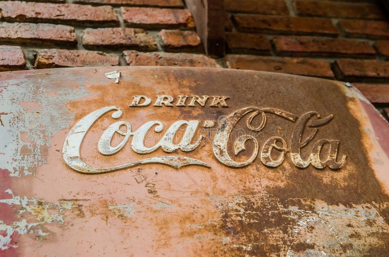 Classic trademark branding logo of CoCa-Cola on rusty metal sheet with red brick wall. royalty free stock images