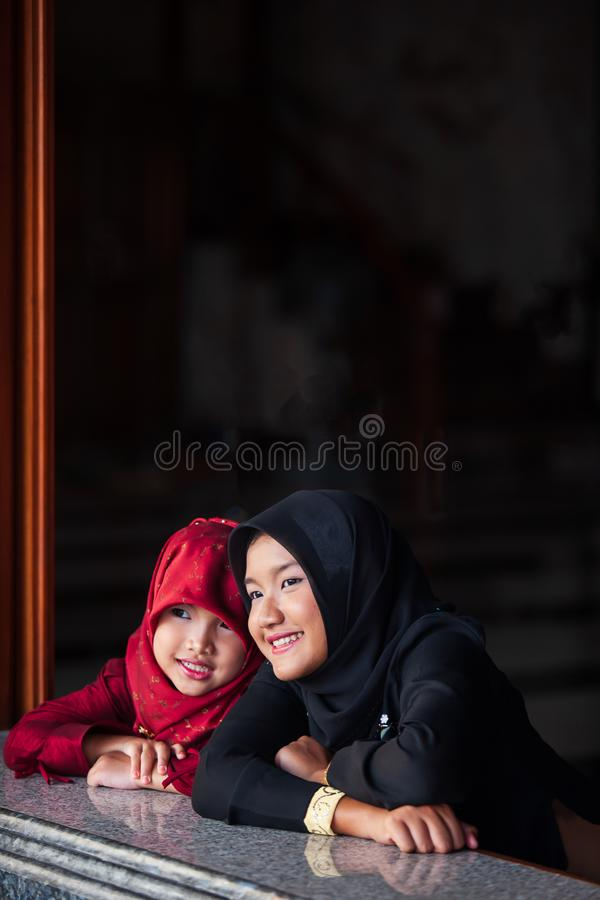 Couple adorable muslim girl in traditional clothing, black and red hijab or niqab and abaya smiling and watching out the window. stock photography