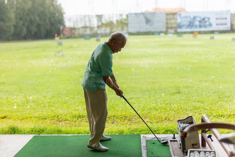 Bangkok Thailand - Übung des älteren Mannes, die sein Golf an der Golfdriving-range übt lizenzfreie stockbilder