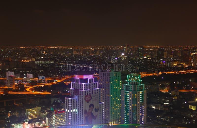 Bangkok Thailand - April 28, 2014 Avbilda visa några byggnader och ljus av staden av Bangkok på natten arkivbilder