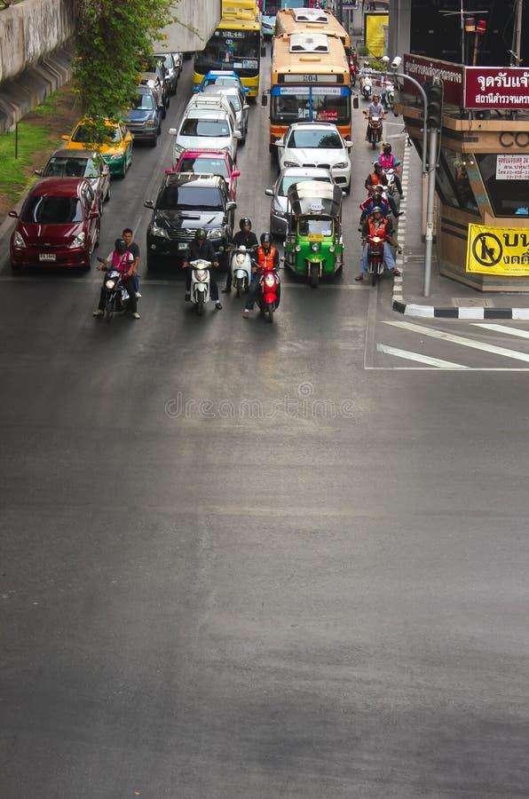 Bangkok Thailand - April 31, 2014 Bilar och motorcyklar i mitt av trafiken som väntar på trafikljuset i staden av royaltyfri foto